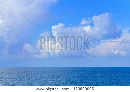 A puffy white, cloudy sky over the sea during a bright day.