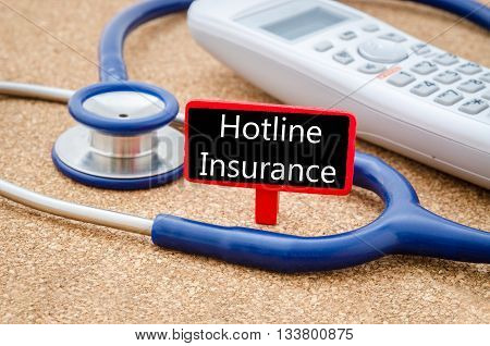 Phone and stethoscope on the table with Hotline insurance words on the board. Medical concept.