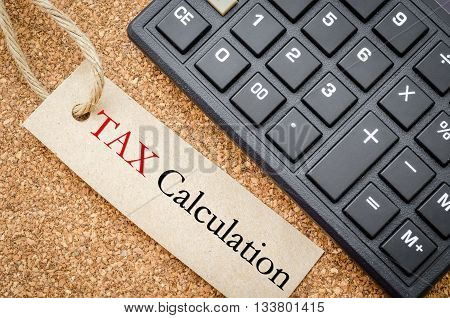 Tax calculation on recycle tag with calculator on wooden desk. Business concept.