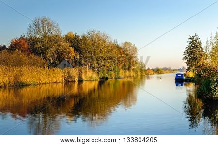Bright and picturesque image of a small Dutch river on a sunny day in autumn. The reeds and the leaves of the trees and shrubs changed already their colors.