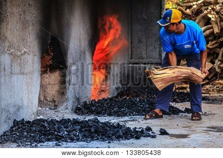 NIZWA, OMAN, MAY 27, 2016: Halwa factory worker is trowing log into a wood fired oven under halwa kettles