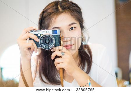 Female photographer taking a photo with mirrorless camera at the coffee art shop