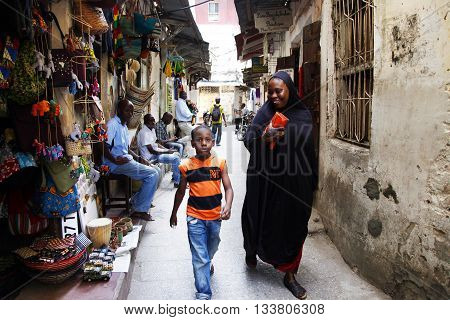 Stone town Tanzania - December 30 2015: Stone Town. Woman in Zanzibar all have to wear black burka when they go outside even girls have to wear scalf on their heads. It is a Muslim life stile. Streets of the town are always lively.