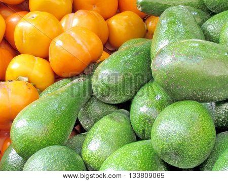 Persimmon and avocado on bazaar in Tel Aviv Israel