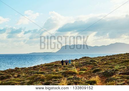 sunrise at the beach and beautiful dramatic sky with clouds in small bay. Chania city , Crete, Greece. Adult family walking along coast line