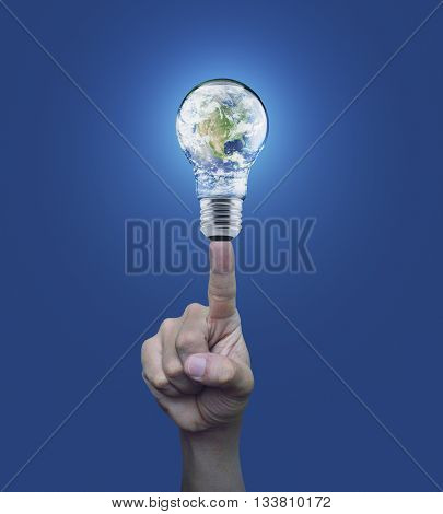 Hand pressing earth globe in light bulb over blue background Energy conservation and environmental concept Elements of this image furnished by NASA