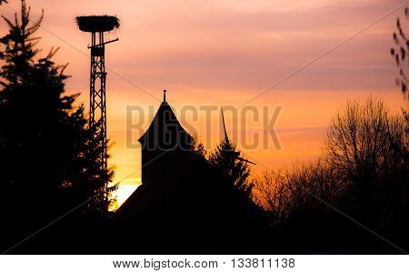 One Stork nest in sunset light, silhouette of stork on sunset, stork in the nest, summertime, sunset with bird nest silhouette