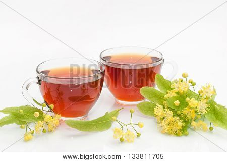 Two glass cups of tea with a sprig of flowering linden isolated on white background