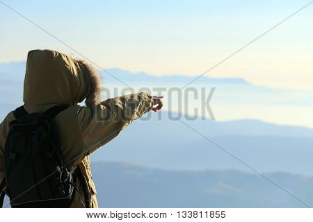 Young Explorer With Winter Jacket And Backpack Indicates The Horizon From Above The Top Of The Mount