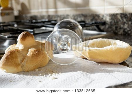 bread roll half cut with a beer glass on a stove-top
