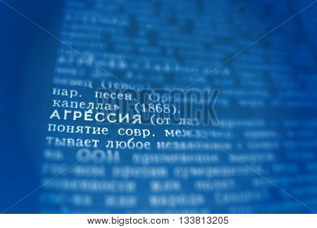 Aggression Definition Word Text in Dictionary Page. Shallow depth of field. Russian language. Blue and white image