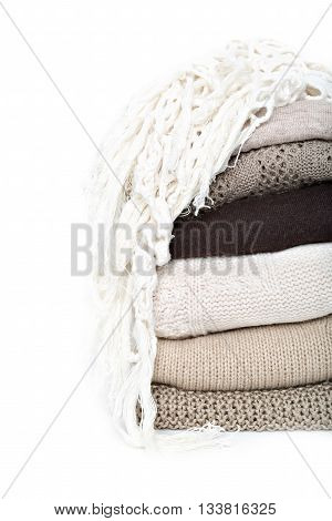 stack of brown woolen knitted sweaters isolated on white background