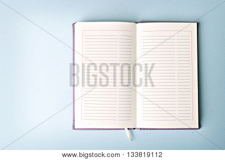 opened notebook on blue table flat lay