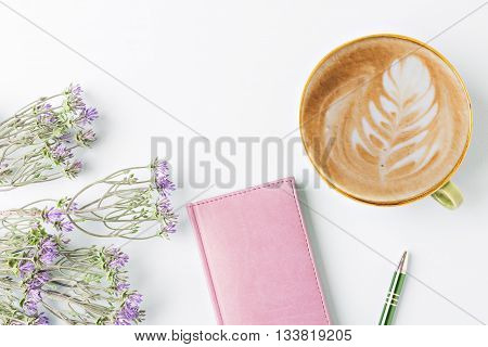 closed notebook with pen and coffee flat lay
