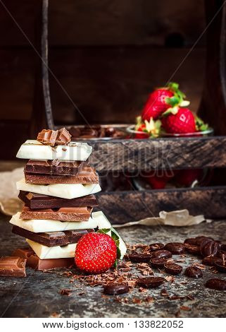 Chocolate / Chocolate bar / chocolate background/chocolate tower and strawberry. Dark background. Selective focus.