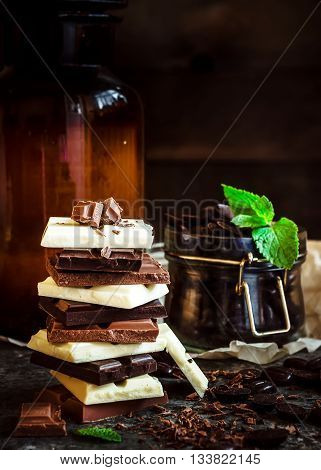 Chocolate / Chocolate bar / chocolate background/chocolate tower and glass with chocolate beans decorated with mint leaf. Dark background. Selective focus.