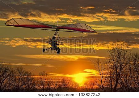The motorized hang glider fly in the sunset