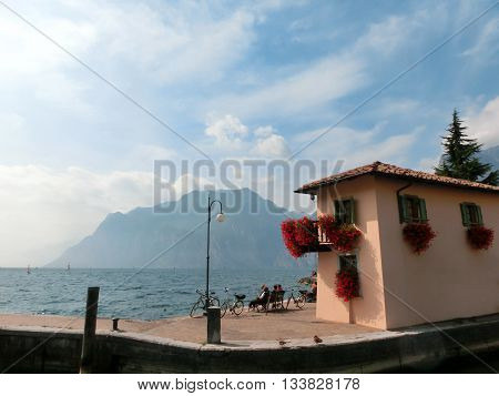 Torbole, Italy - September 21, 2014: Lake Garda boardwalk with houses, tourists in Torbole, Italy. Torbole is one of the most popular towns on Garda Lake, known as a wind surfers paradise.