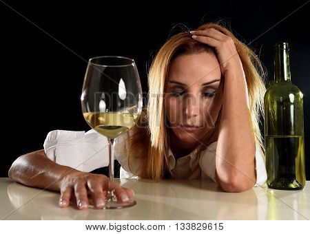 drunk blond woman alone in wasted depressed expression taking a nap suffering hangover holding glass isolated on black background in alcohol abuse and alcoholic housewife concept