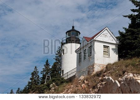 Bass Harbor lighthouse sits atop a rocky cliff in Acadia maine.