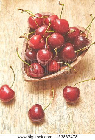 Cherries on wooden board. Top view with copy space. Tonned photo.