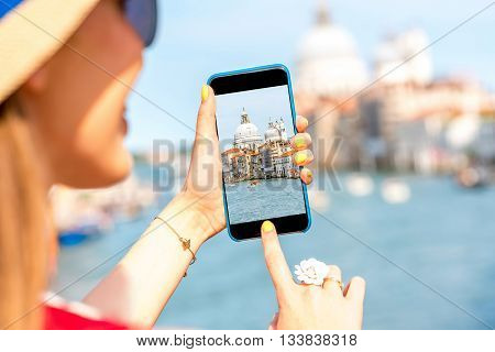 Woman photographing with smart phone beautiful Grand canal with Santa Maria della Salute basilica in Venice.
