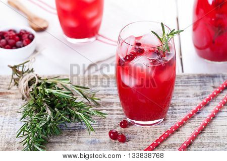 Cranberry and rosemary lemonade, cocktail, fizz on a wooden background.