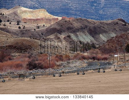 A peaceful drive on an Eastern Oregon back road passes a large wheel line on a farm located in a canyon of multi colored hills.
