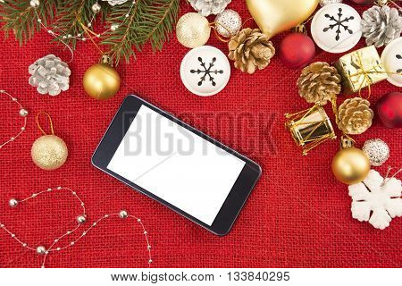 Mobile phone and the Christmas decoration on a red burlap background