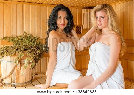 Beautiful Woman Sitting In A Sauna Near The Tub And Brooms
