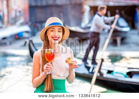 Young woman with glass of Spritz Aperol and italian snacks cicchetti sitting near the water chanal with gondolier and gondola on the background in Venice. Image with small depth of field