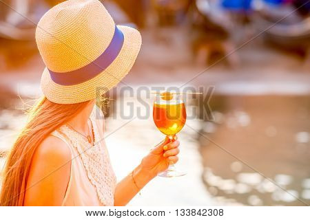 Young woman with glass of Spritz Aperol sitting near the water chanal in Venice on the sunset. Traditional italian appetizer drink. Image with small depth of field