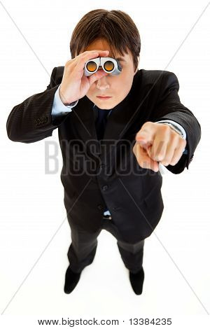 Serious businessman looking through binoculars and pointing finger at you isolated on white