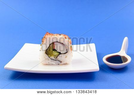 sushi piece and soy sauce on blue background