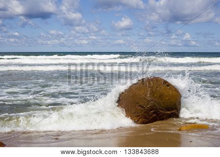 One big stone at sea coast with waves and foam