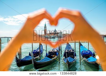 Heart shape made with hands with beautiful view on gondolas and San Giorgio Maggiore island in Venice. Venice is one of the favorite tourist city