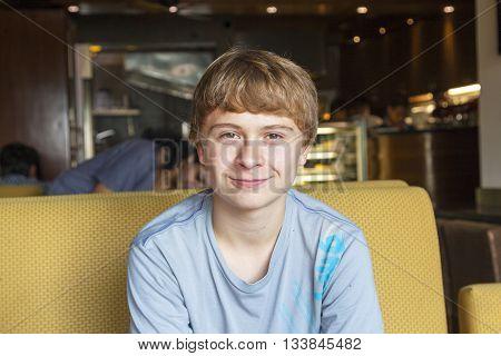 Smart Boy Sitting In A Fastfood Restaurant