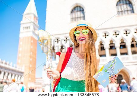 Young female traveler having fun with carnaval mask and tourist map on San Marco square in Venice. Happy traveling in Venice