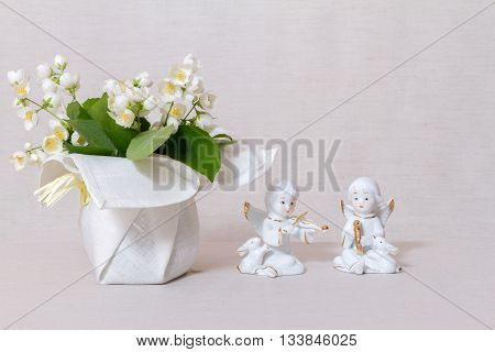 Jasmine flowers in a vase with a textile coating and figurines of angels