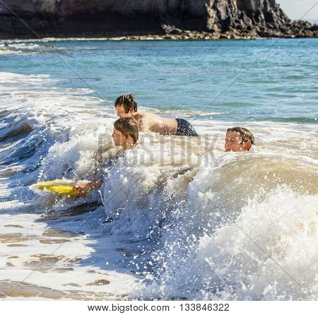 boys have fun riding in the waves in Lanzarote
