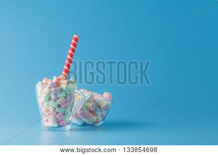 Sweet candies in bowl on blue color table