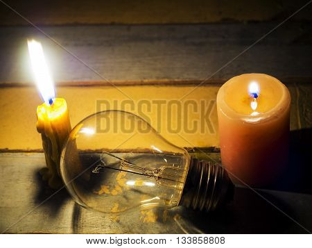 candle light shine on incandescent bulb; no electricity makes electrical equipment useless