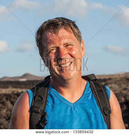 man on walking trail in volcanic area in Lanzarote looks happy