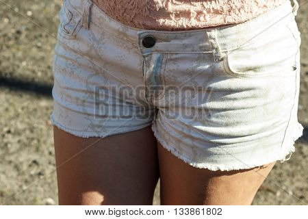 Closeup of sexy alluring woman hips. Slim girl wearing jeans shorts. Hotness and sexiness.