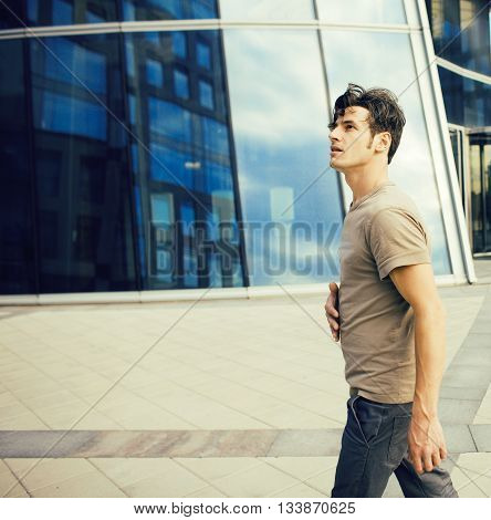 young man stand in front of modern business building, dreams come true