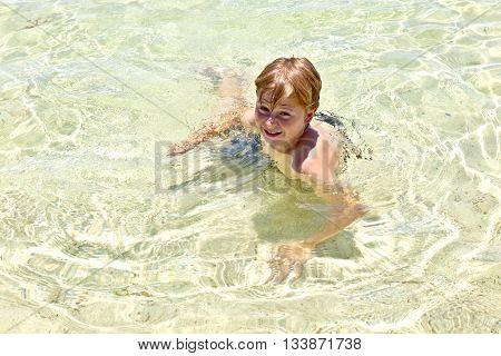 Boy In The Ocean Swims In Beautiful Clear Water