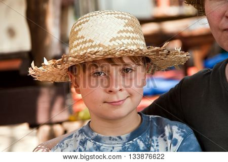 Boy With Straw Hat Has A Rest In The Sun At An Open Air Restaurant