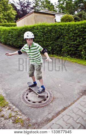 young boy enjoys riding on his skate board