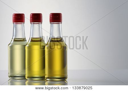 sesame seed oil, olive oil, grape seed oil and corn oil in  glass bottle over white background