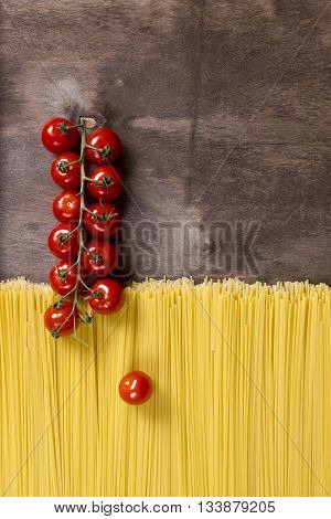 Spaghetti and tomatoes on a dark wooden background
